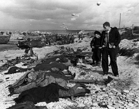 FRANCIA—Pescadores franceses observan los cuerpos de soldados muertos durante el desembarco en las playas de Normandía, junio 1944