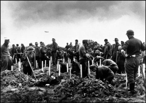 FRANCIA—Prisioneros alemanes entierran a hombres muertos durante el desembarco en Omaha Beach, junio 1944