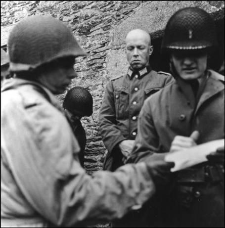 FRANCIA—Un oficial alemán se rinde ante oficiales americanos, junio 1944